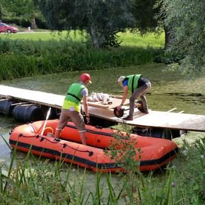 På billedet ses 2 deltagere fra et hold i fuld gang med at pakke deres gummibåd til Tongo