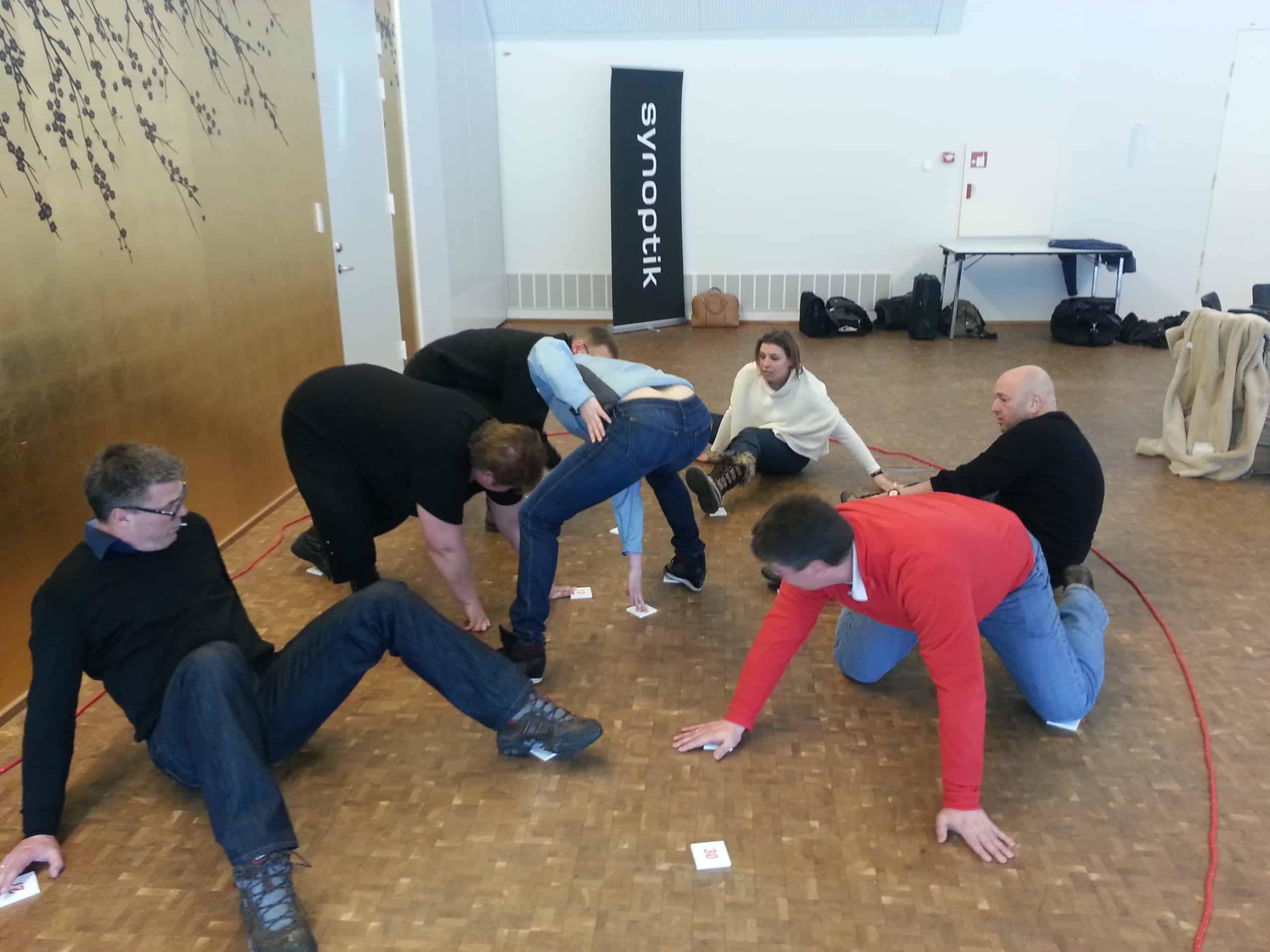 På billedet ses en gruppe igang med en teambuilding øvelse på jorden