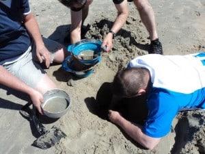 Her ses et billede af nogle deltager som graver et hul i sandet