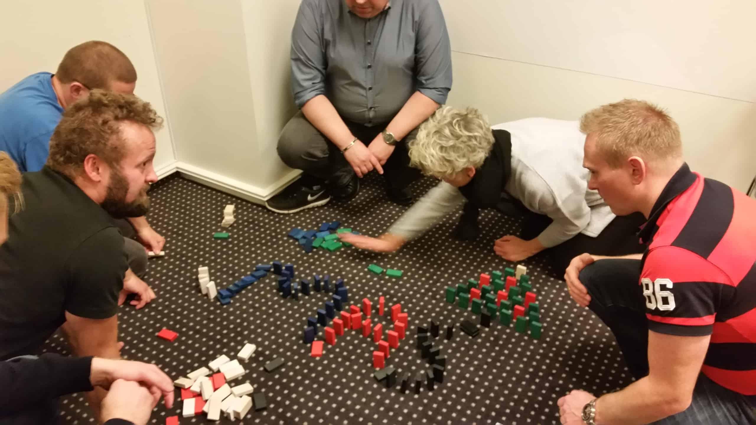 På billedet ses 5 personer som er ved at sætte domino brikker op
