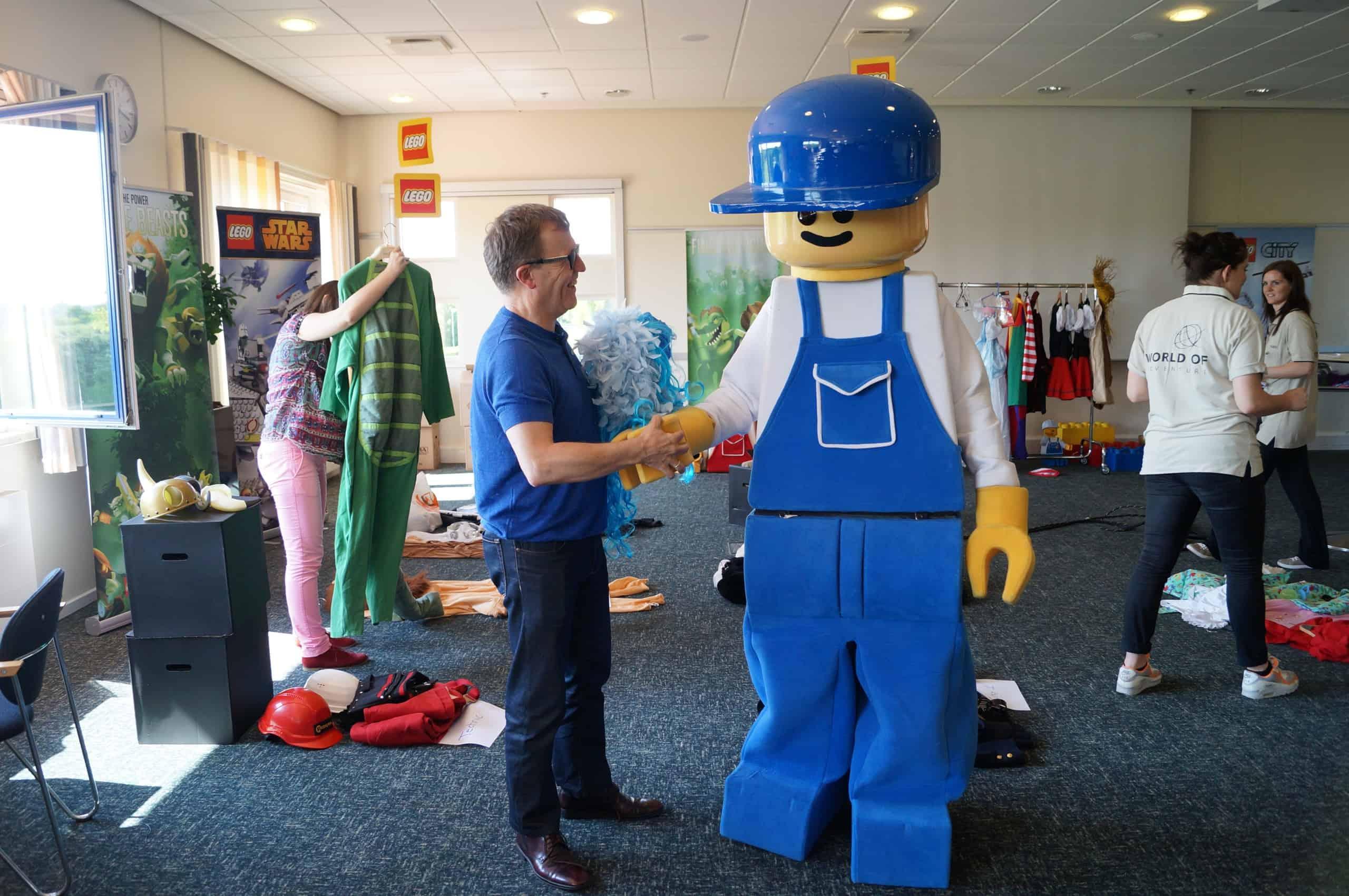 En mand der giver hånd til legomanden fra Lego