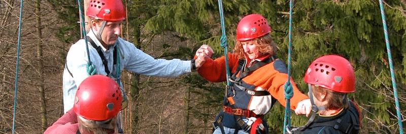 På billedet ses nogle deltager i fuld gang med at hjælpe hinanden i klatreudstyr