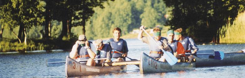 Her ses to kanoer med deltager i færd med at sejle langs en å