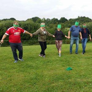 Deltagere med blind for øjnene i færd med at udføre opgaverne på deres teambuilding øvelse adventureløb