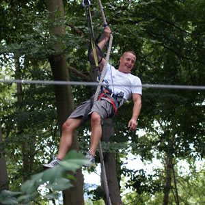 En mand hængende i et reb i klatreparken