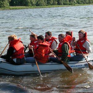 Deltagere i fuld gang med at sejle en gummibåd