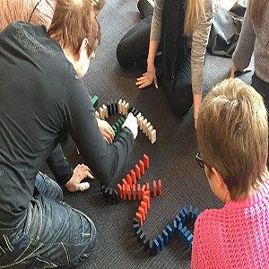 På billedet ses en gruppe i fuld gang med at opstille domino klodser