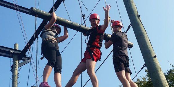På billedet ses 3 deltager i fuld gang med at hjælpe hinanden med at klatre