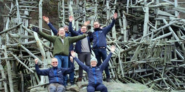 På billedet ses en gruppe ansatte med armene i vejret efter en dag med belbins teamrolle analyse