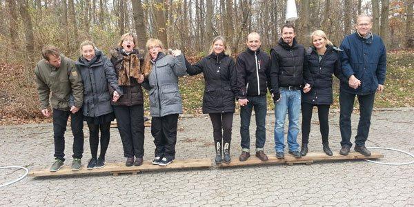 På billedet ses deltagere på en teamdag i fuld gang med at få en planke til at balancere med deres egen kropsvægt