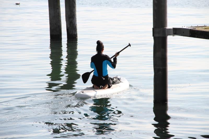 På billedet ses en kvinde, der sidder på et paddle board