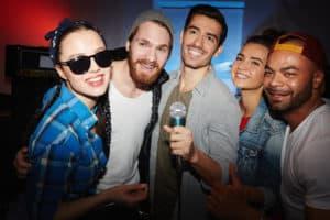 Deltagerne på billedet står med en mikrofon i hånden og udfører aktiviteten Hit med sangen