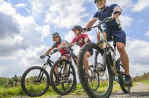 På billedet ses tre personer, som kører på mountain biking