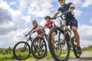 Three people are mountain biking