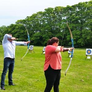 På billedet ses 2 deltagere i fuld gang med at skyde bue & pil